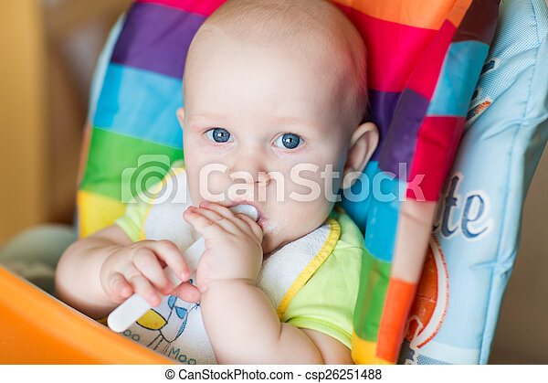 Adorable baby eating in high chair - csp26251488