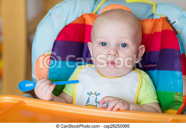 Adorable baby eating in high chair - csp26250995