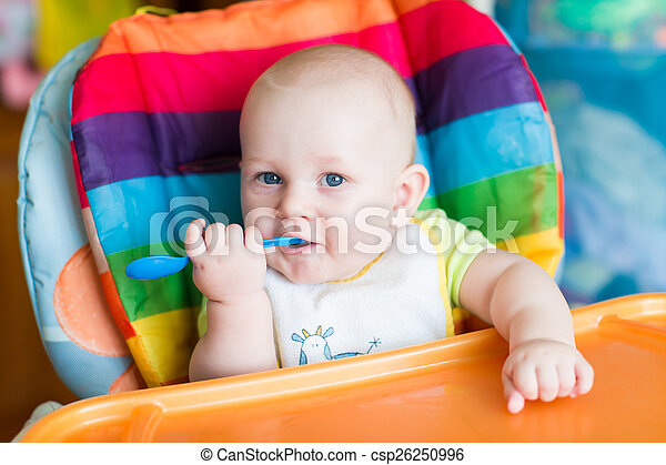 Adorable baby eating in high chair - csp26250996