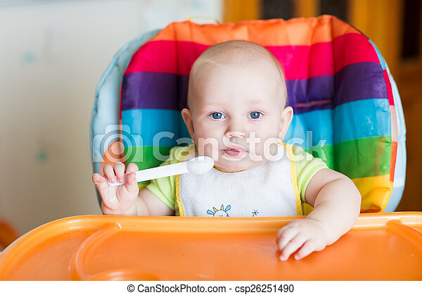 Adorable baby eating in high chair - csp26251490