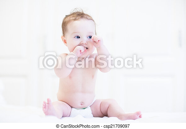 Adorable baby sitting in a white nursery - csp21709097
