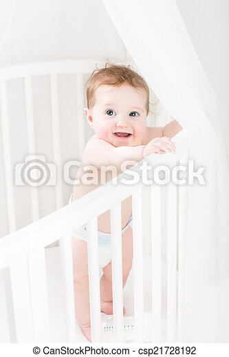 Adorable baby wearing a diaper standing in a white round crib - csp21728192