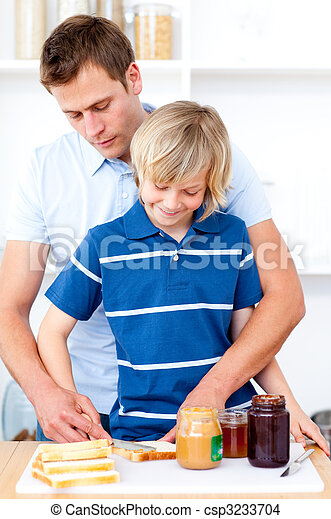 Adorable boy and his father preparing breakfast - csp3233704