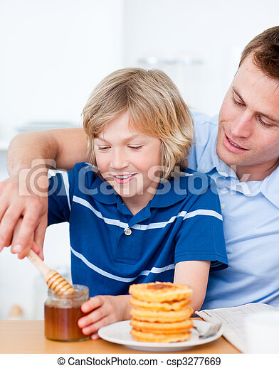 Adorable boy and his father putting honey on waffles - csp3277669