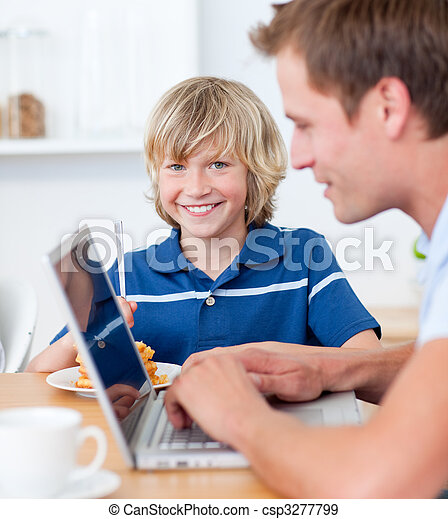 Adorable boy having breakfast while his father using a laptop - csp3277799