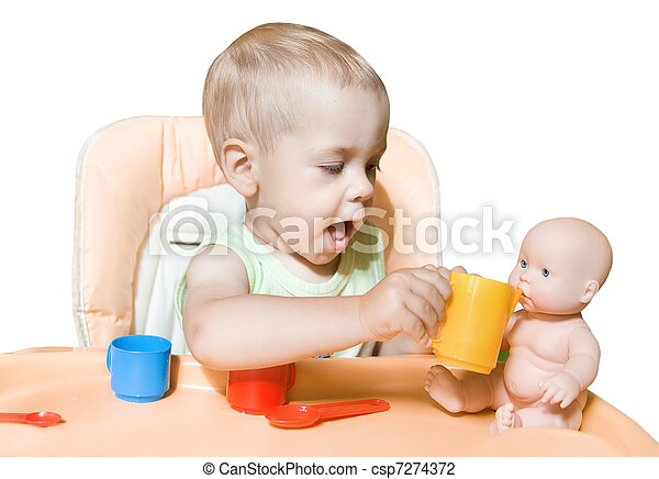Adorable child independently feeding doll sitting in front of the table. Kid's role playing in two years. Over white - csp7274372