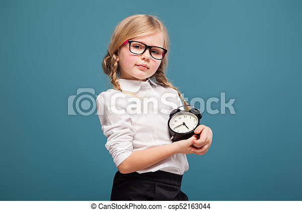 Adorable cute little girl in white shirt, glasses and black trousers hold alarm clock - csp52163044