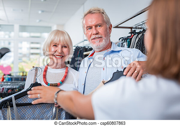 64b25a33e6 Adorable elderly couple in front of cashier desk. Paying for clothes ...