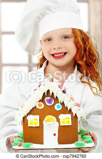 Adorable girl child in chef uniform holding a ginger bread, gingerbread house over white background. - csp7942760