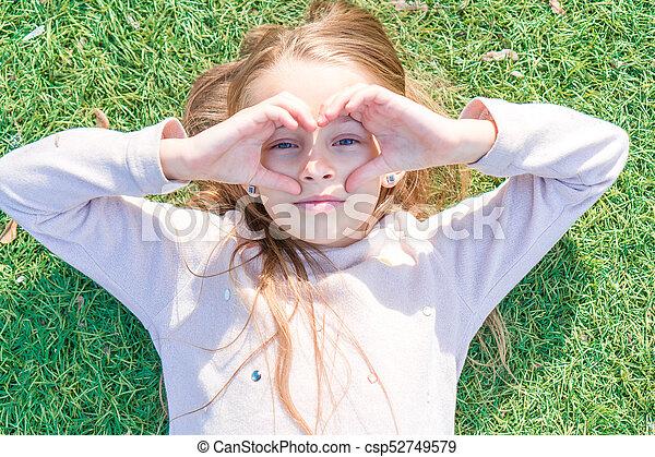 Adorable happy girl on green grass - csp52749579