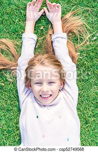 Adorable happy girl on green grass - csp52749568