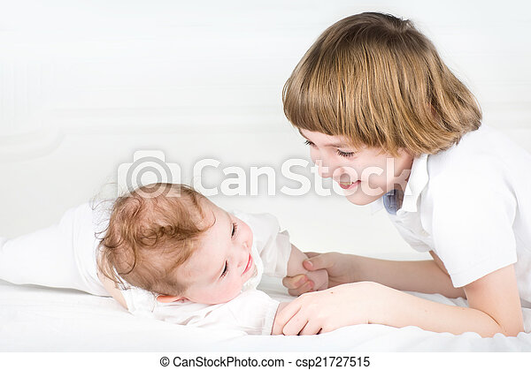 Adorable little baby girl playing with her big brother - csp21727515