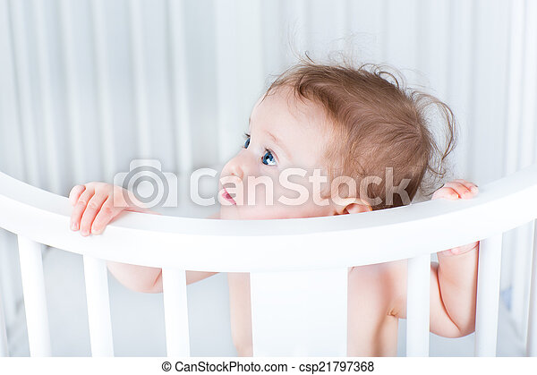 Adorable little baby standing in a beautiful round white crib on - csp21797368