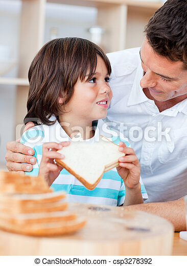 Adorable little boy and his father eating bread - csp3278392