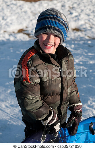 dd8de9c21 Adorable little boy holding sled smiling at camera wearing camo ...