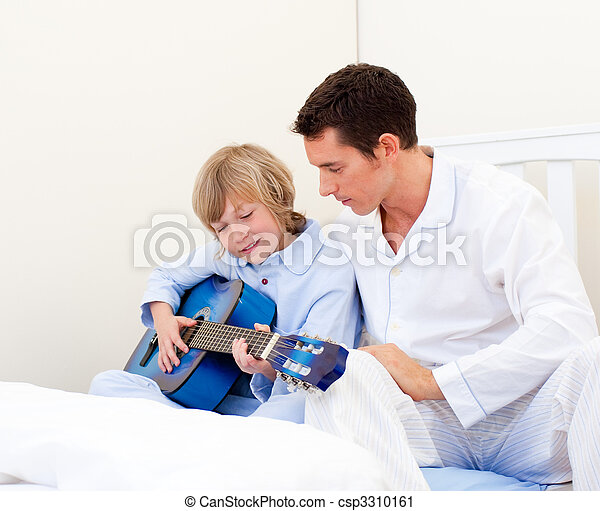 Adorable little boy playing guitar with his father - csp3310161