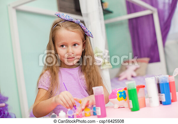 Adorable Little girl draws paints at her table in the room - csp16425508