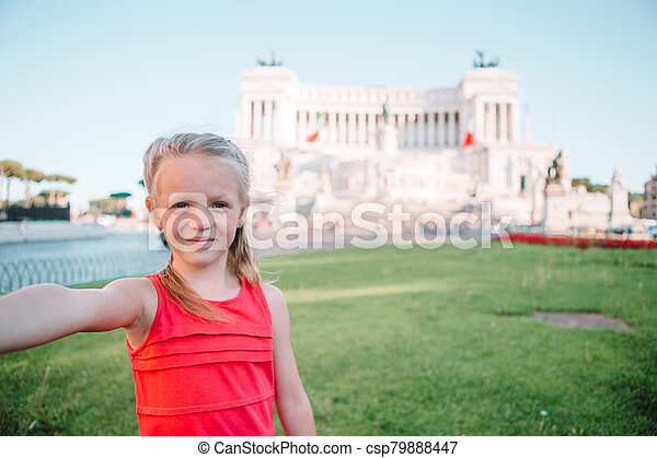 Adorable little girl taking selfie in front of Altare della Patria, Vittoriano, Rome, Italy. - csp79888447