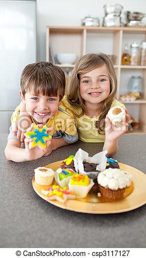 Adorable siblings showing their cookies - csp3117127