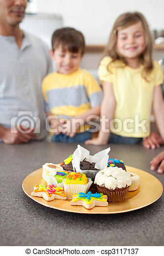 Adorable siblings showing their cookies in the kitchen - csp3117137