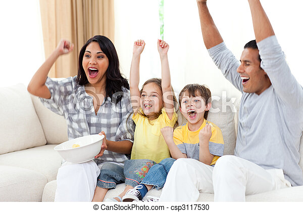 Adorable siblings watching TV with their parents - csp3117530