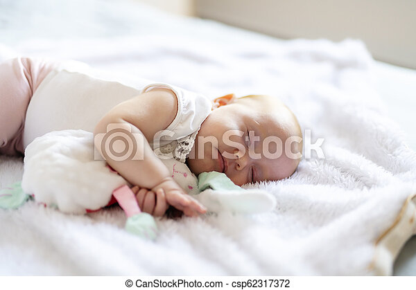 Adorable two months baby girl relaxing in bedroom on knitted blanket on a sunny morning - csp62317372