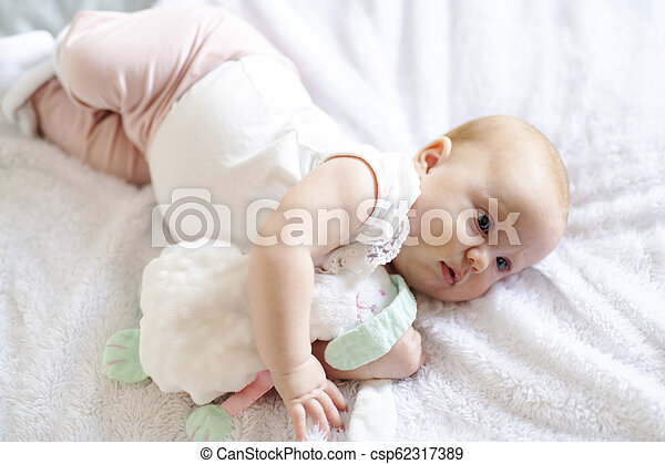 Adorable two months baby girl relaxing in bedroom on knitted blanket on a sunny morning - csp62317389