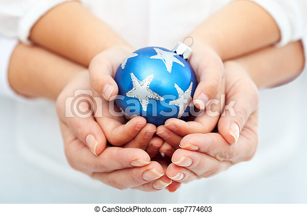 Adult and child hands holding christmas bauble - csp7774603