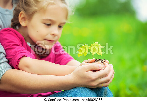 Adult and child holding little green plant in hands - csp46026388