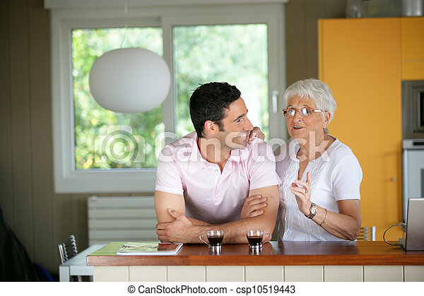 Adult man with his mother in a kitchen - csp10519443