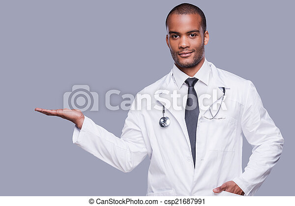 Advertising your product. Confident African doctor holding copy space and looking at camera while standing against grey background - csp21687991