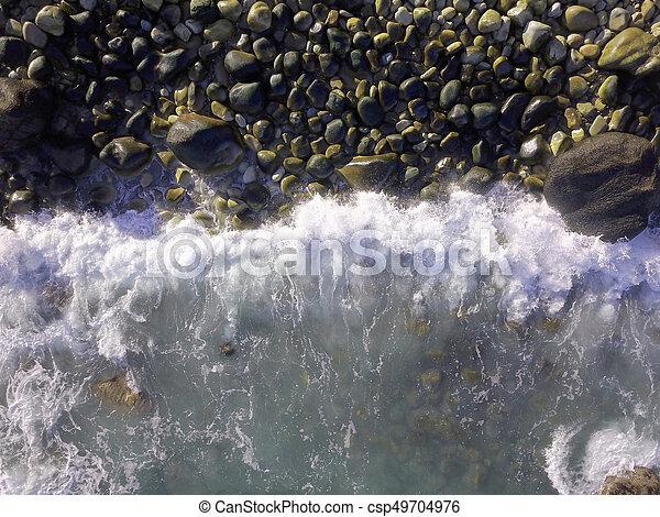 Aerial over waves crashing into a rocky beach - csp49704976