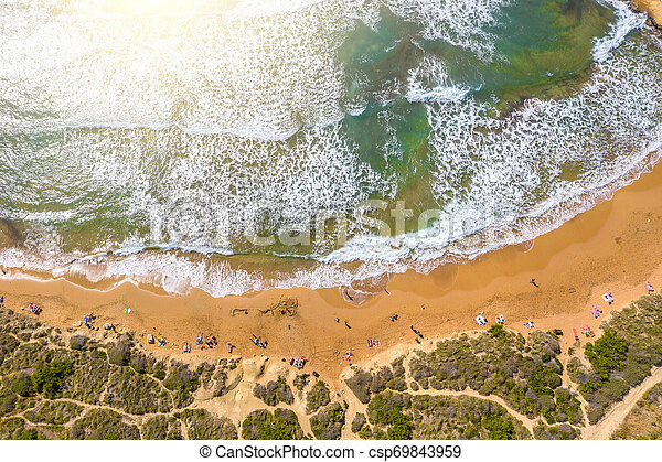 Aerial vew From fying drone view of the wild beach with sunbathers resting people. - csp69843959