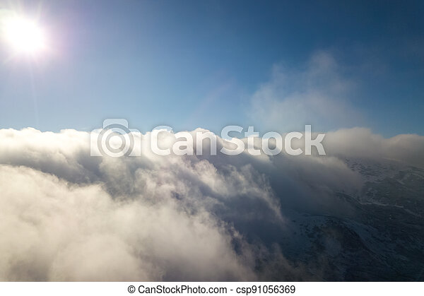 Aerial view from above of white puffy clouds in bright sunny day. - csp91056369