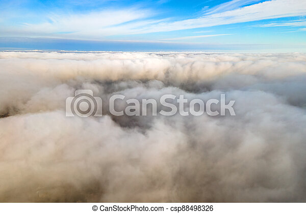Aerial view from above of white puffy clouds in bright sunny day. - csp88498326