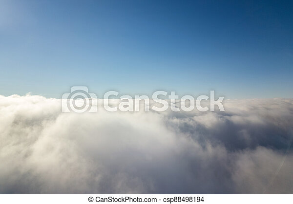 Aerial view from above of white puffy clouds in bright sunny day. - csp88498194