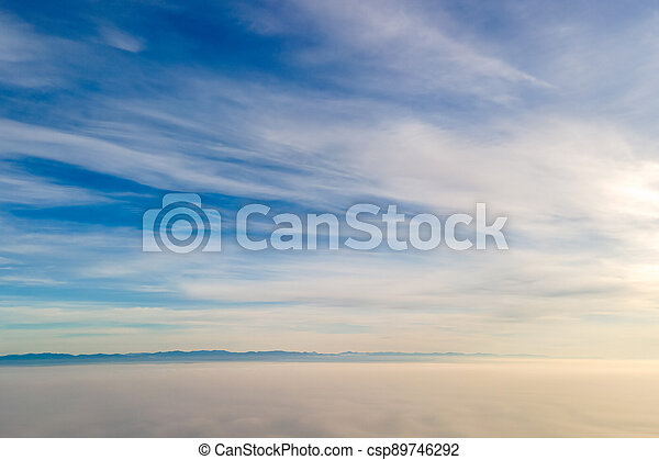 Aerial view from above of white puffy clouds in bright sunny day. - csp89746292