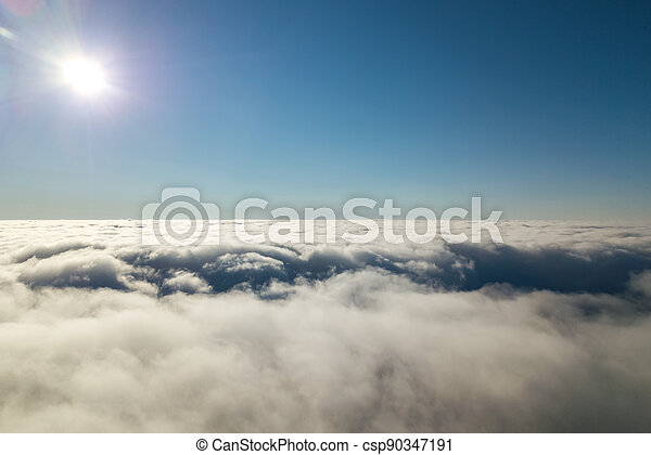 Aerial view from above of white puffy clouds in bright sunny day. - csp90347191