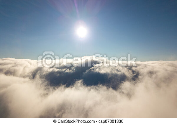 Aerial view from above of white puffy clouds in bright sunny day. - csp87881330
