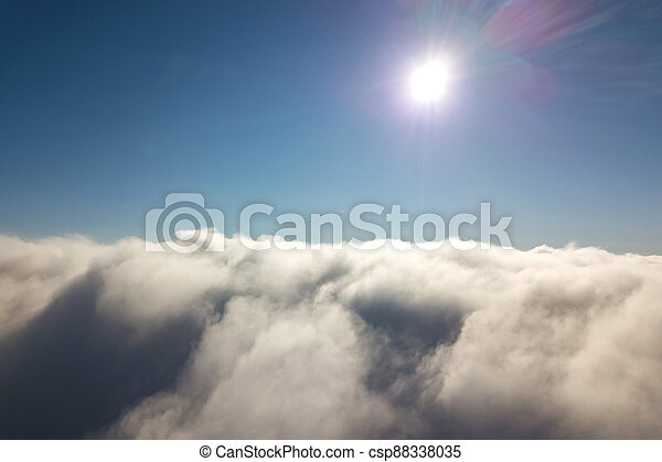 Aerial view from above of white puffy clouds in bright sunny day. - csp88338035