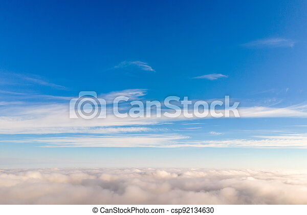 Aerial view from above of white puffy clouds in bright sunny day. - csp92134630