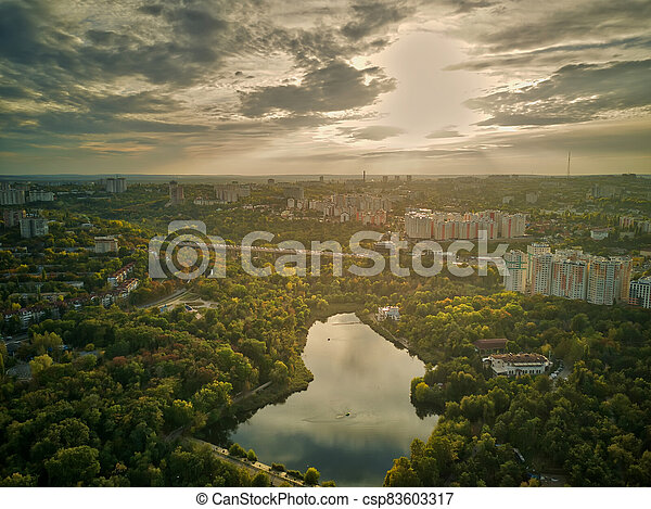 Aerial view of a lake in a park with autumn trees. Kishinev, Moldova. Epic aerial flight over water. Colorful autumn trees in the daytime. - csp83603317