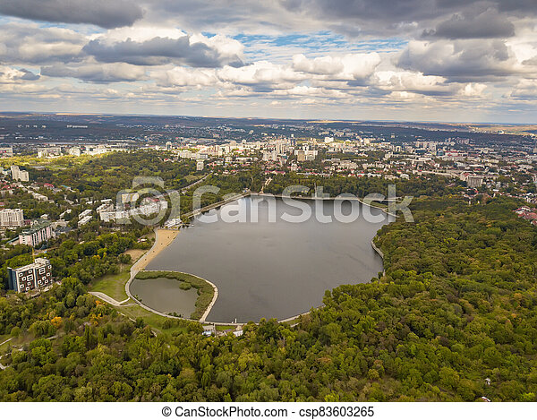 Aerial view of a lake in a park with autumn trees. Kishinev, Moldova. Epic aerial flight over water. Colorful autumn trees in the daytime. - csp83603265