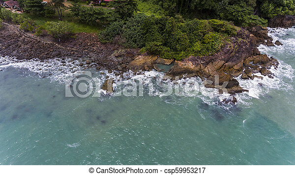 Aerial view of a rocky and green beach shore. - csp59953217