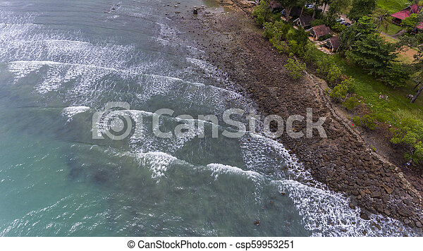 Aerial view of a rocky and green beach shore. - csp59953251