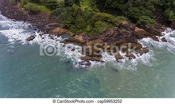 Aerial view of a rocky and green beach shore. - csp59953252
