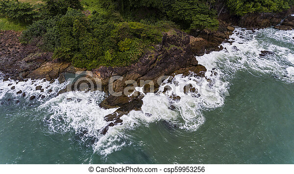 Aerial view of a rocky and green beach shore. - csp59953256