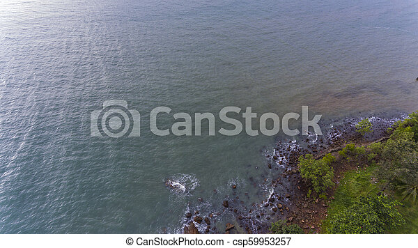 Aerial view of a rocky and green beach shore. - csp59953257