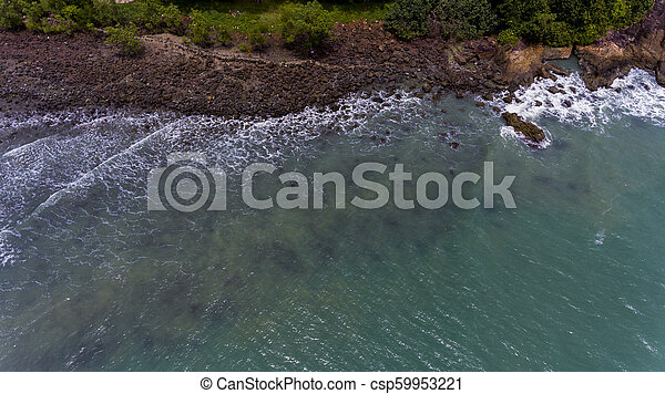 Aerial view of a rocky and green beach shore with blue water - csp59953221