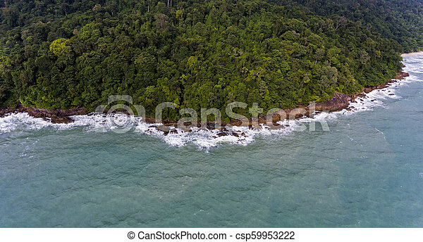 Aerial view of a rocky and green beach shore with blue water - csp59953222